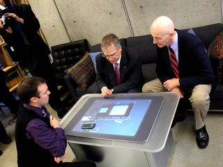 Mohawk's Justin Fyfe (l) gives a demo of the Surface computer to the Hon. Gary Goodyear and MP David Sweet.